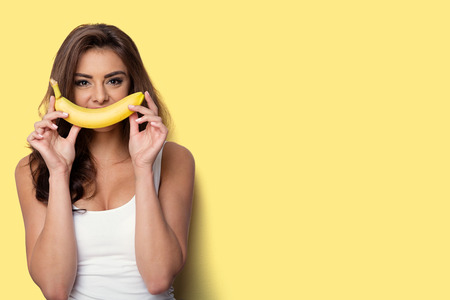 Photo for woman making fun with a banana. yellow background - Royalty Free Image