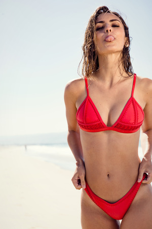 Photo for young woman at the beach sticking out tongue. - Royalty Free Image