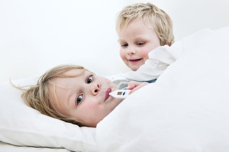 Sick young boy measuring his fever with a thermometer in bed, whilst his younger brother is trying to cheer him up