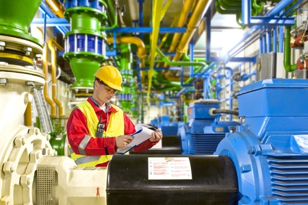 Photo pour Engineer looking aty a checklist during maintenance work in a large industrial engine room - image libre de droit