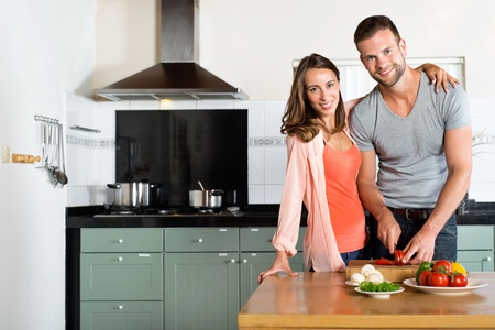 Photo pour Portrait of happy young couple cutting vegetables at kitchen counter - image libre de droit