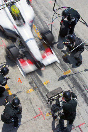 Photo for Professional pit crew ready for action as their team's race car arrives in the pit lane during a pitsstop of a car race, concept of ultimate teamwork - Royalty Free Image