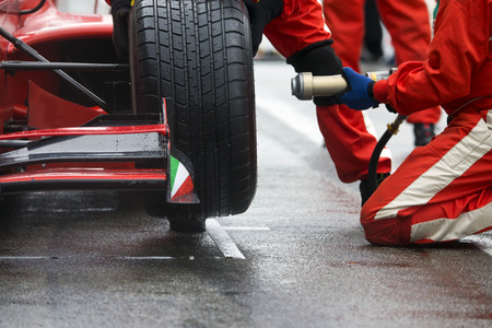 Photo pour Professional racing team at work during a pitstop of a race car in the pitslane during a car race. - image libre de droit