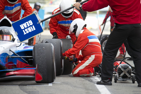 Photo for Teamwork and professionalism during the skillful tire change at a car race pitstop - Royalty Free Image
