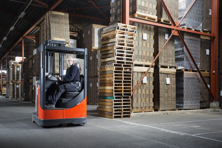 Photo pour Reach truck driver in a warehouse where pallets and cardboards are stored - image libre de droit