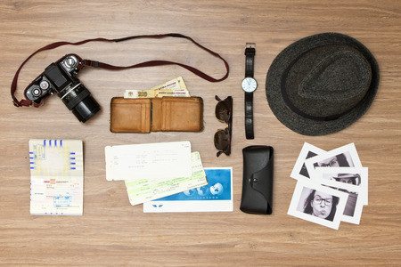 Foto de International travel background with a retro or vintage touch. Items include an old photo camera, passport, wallet with foreign currency, airplane ticket, hat, sunglasses and a couple of black and white photos - Imagen libre de derechos