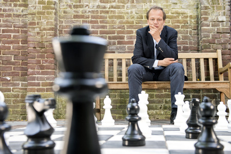 Foto de Concentrated man, thinking strategically about his next move, sitting on a wooden bench in front of a brick wall during an outdoor chess game using life sized chess pieces and chess board - Imagen libre de derechos