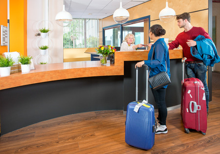 Photo pour Young couple at the check in counter of a hotel,having just arrived with their luggage from the airport - image libre de droit