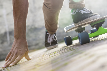 Cropped image of man skateboarding on footpath during summer