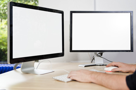 Foto de Two computer monitors with a white screen on a desk, with a man's hands on a keyboard in an office, suited for mock-ups and presentations, with plenty of copy space for your designs - Imagen libre de derechos