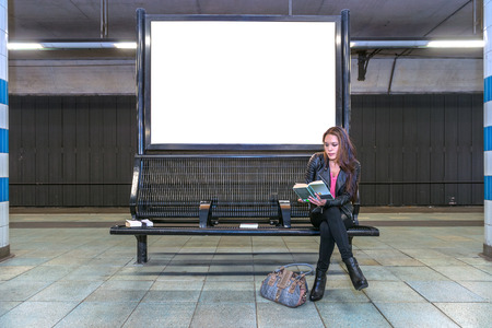 Foto de A blank billboard at an underground railway station with a woman sitting on a bench underneath, reading a book - Imagen libre de derechos