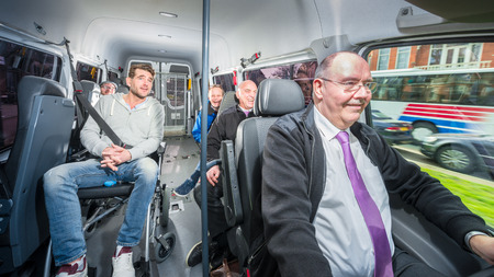 Foto per Group of people, traveling in a minivan with a disabled person in a wheel chair, surrounded by several others - Immagine Royalty Free