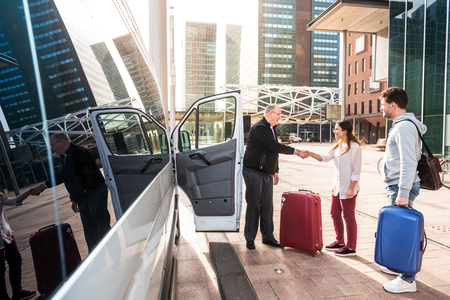 Photo for Driver of a airport shuttle minivan, greeting his passengers with their luggage on the sidewalk of a modern city business district - Royalty Free Image