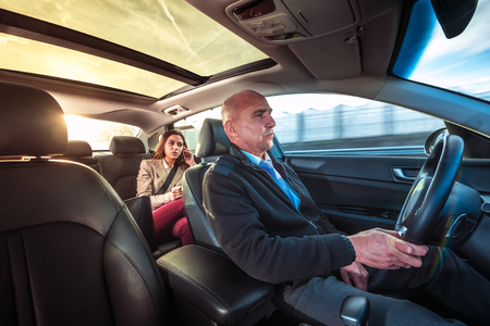 Photo pour Professional driver, a taxi chauffeur, driving a woman towards her destination. - image libre de droit