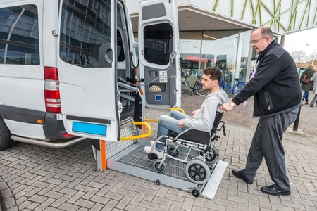 Photo pour Side view of taxi driver assisting man on wheelchair to board van outside building - image libre de droit