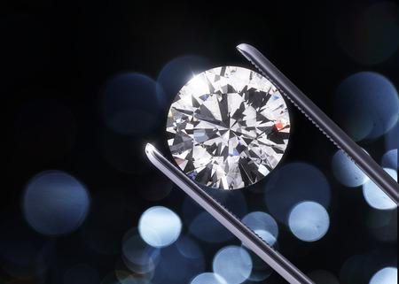 Photo pour Luxury diamond in tweezers closeup with dark background - image libre de droit