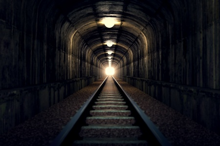 A railroad tunnel with a light at the end.