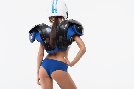 Photo pour Back view of isolated sexy young woman in American football shoulder pad and helmet protection with hand on belt - image libre de droit