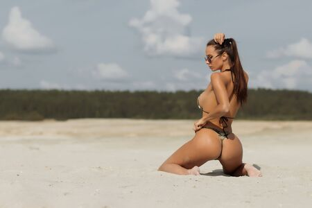 Photo for Back view of sexy young woman with perfect buttocks wearing swimwear with thongs doing ponytail while kneeling on sandy beach on resort - Royalty Free Image