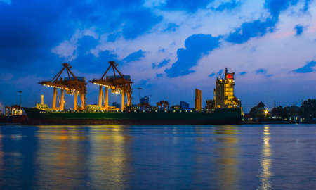 Container Cargo freight ship with working crane bridge in shipyard at dusk for Logistic Import Export