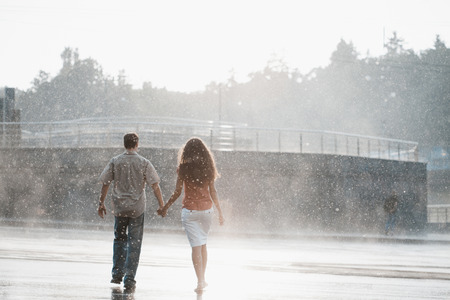 couple in love hugging and kissing under summer rain