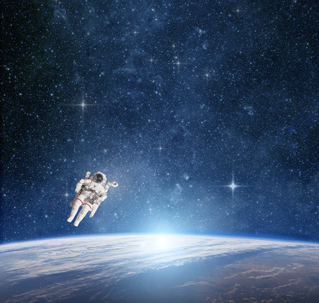 Astronaut in outer space against the  planet earth.