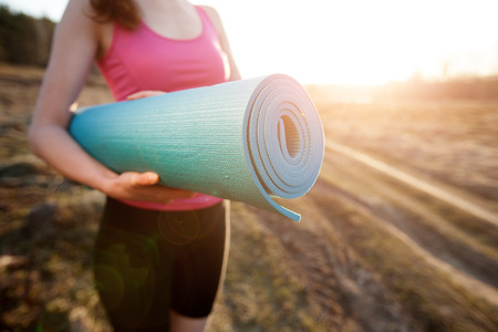 Photo pour woman walking with a yoga mat outside during sunset n a rural area wearing sports wear and doing yoga - image libre de droit