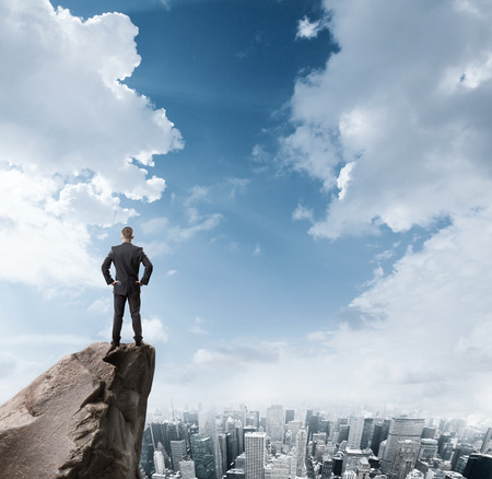 Foto de Young businessman standing on edge of rock mountain and looking at the city - Imagen libre de derechos