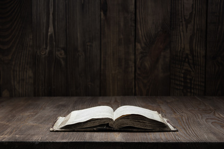 Photo pour Image of an old  Holy Bible on wooden background on a wooden background in a dark space - image libre de droit