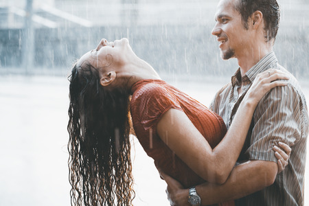 The girl with the boy run under a downpour rain
