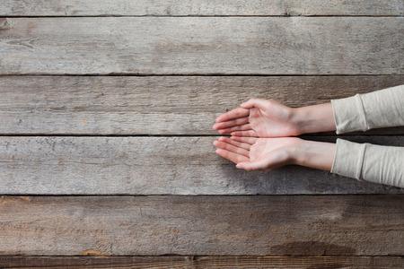 Foto de woman hands with open palms over wooden table - Imagen libre de derechos