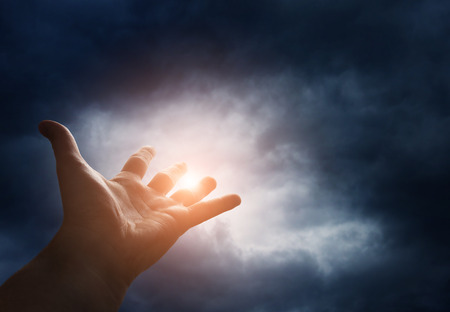 Photo pour Hand reaching for the  sky with dark stormy clouds - image libre de droit