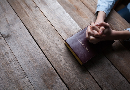 Photo pour hands praying with a bible in a dark over wooden table - image libre de droit