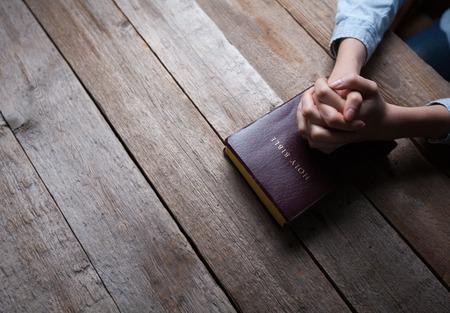 Foto de hands praying with a bible in a dark over wooden table - Imagen libre de derechos