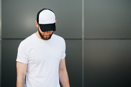Foto de Hipster wearing white blank t-shirt and a cap with space for your logo - Imagen libre de derechos