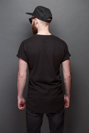 Foto de Hipster handsome male model with beard wearing black blank t-shirt with space for your logo or design over gray background - Imagen libre de derechos