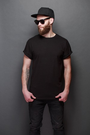 Photo pour Hipster handsome male model with beard wearing black blank t-shirt with space for your design over gray background - image libre de droit