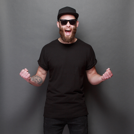 Foto de Hipster handsome male model with beard wearing black blank t-shirt with space for your design over gray background - Imagen libre de derechos