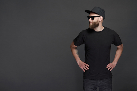 Photo for Hipster handsome male model with beard wearing black blank baseball cap with space for your logo - Royalty Free Image