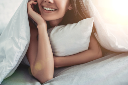 Foto de Cropped image of beautiful smiling young woman covered by blanket while lying on bed - Imagen libre de derechos
