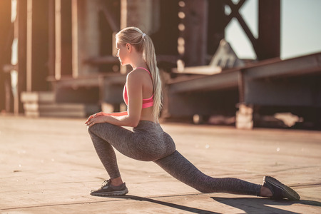 Photo for Attractive sporty girl is stretching on street during the sunset - Royalty Free Image