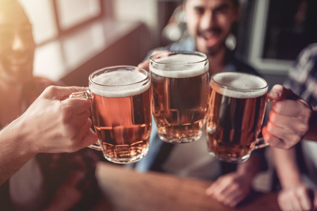 Photo for Cheers, my friends! Cropped image of three handsome men are drinking beer, celebrating meeting and smiling. - Royalty Free Image