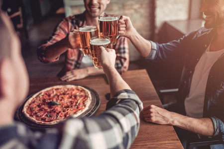 Foto de Cheers! Side view of three male friends in bar drinking beer and eating pizza. - Imagen libre de derechos