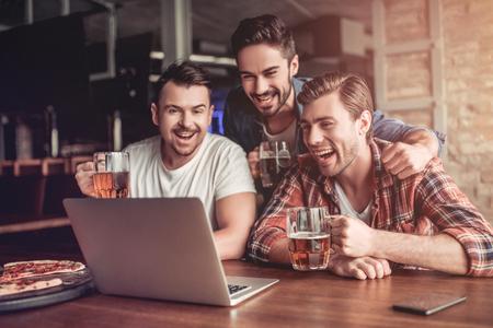 Foto de Happy excited fans are looking into the laptop, drinking beer and smiling. - Imagen libre de derechos