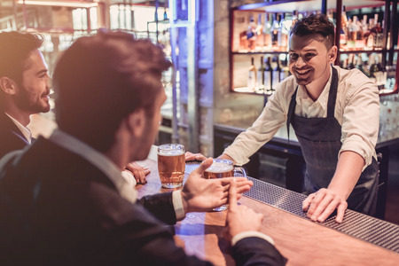 Photo for Handsome businessmen in bar are drinking beer and communicating with cheerful bartender. - Royalty Free Image