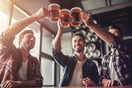 Foto de Cheers, my friends! Three handsome men are drinking beer, celebrating meeting and smiling. - Imagen libre de derechos