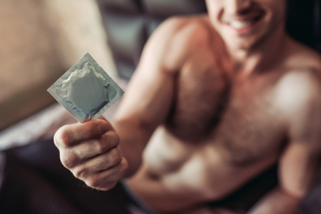 Photo pour Cropped image of a smiling man holding condom in hand while lying on bed. - image libre de droit