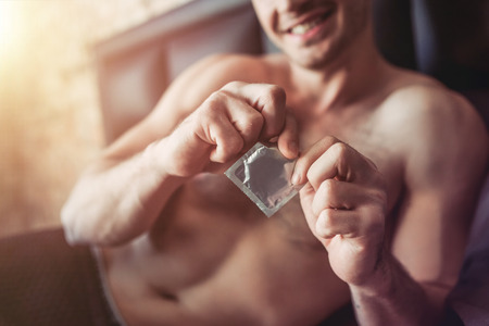 Foto de Cropped image of a smiling man holding condom in hand while lying on bed. - Imagen libre de derechos