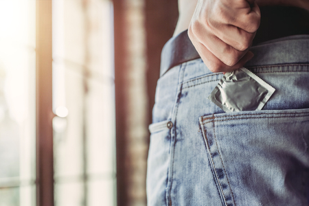 Foto de Cropped image of a man holding condom in hand while taking it from jeans. - Imagen libre de derechos