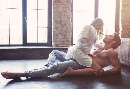 Photo pour Passionate couple in bedroom is having sex on floor. - image libre de droit